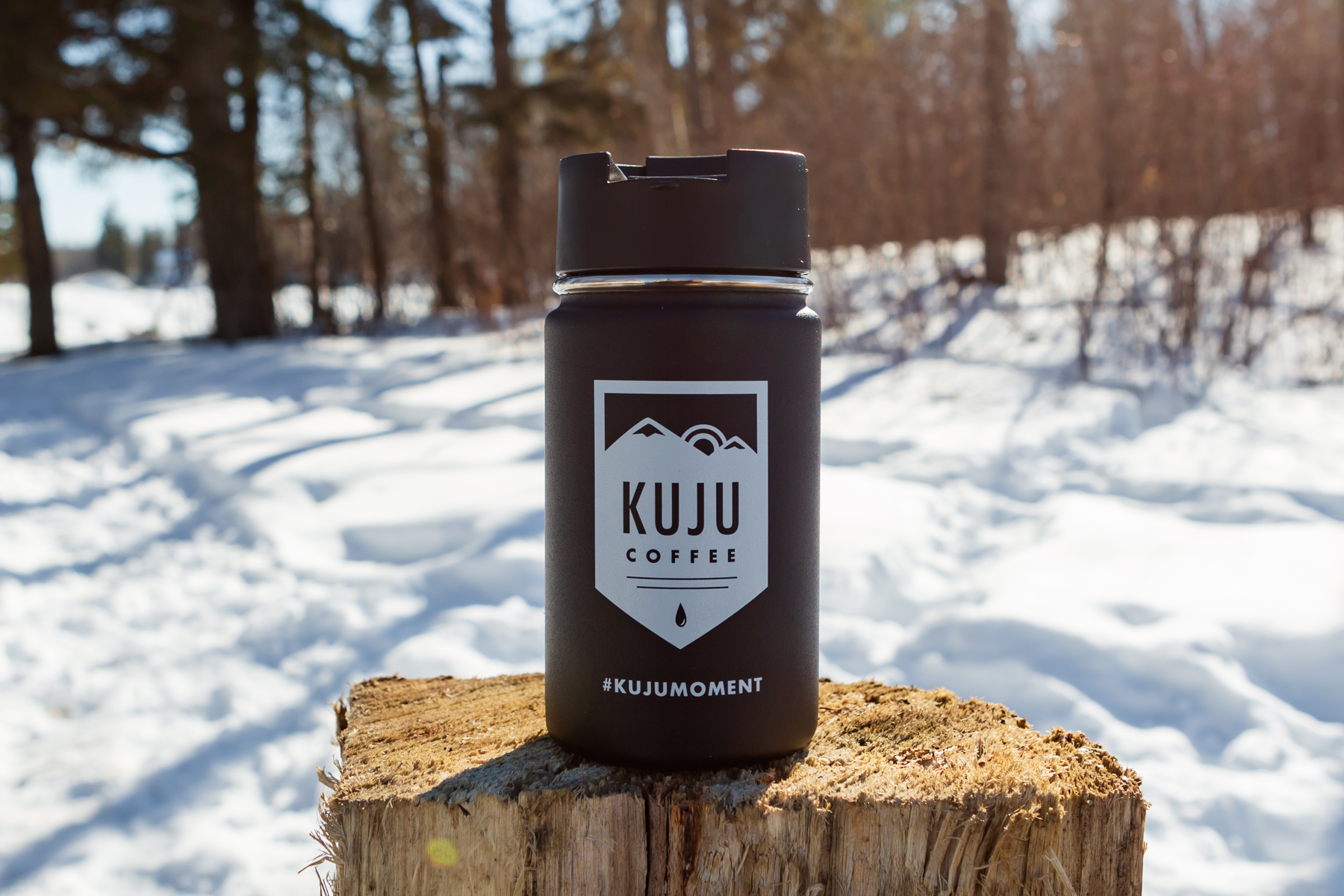 Kuju Coffee Hydro Flask sitting on a log