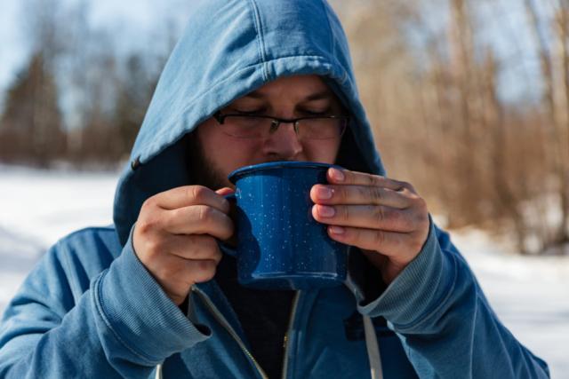 man drinking coffee from enamel mug