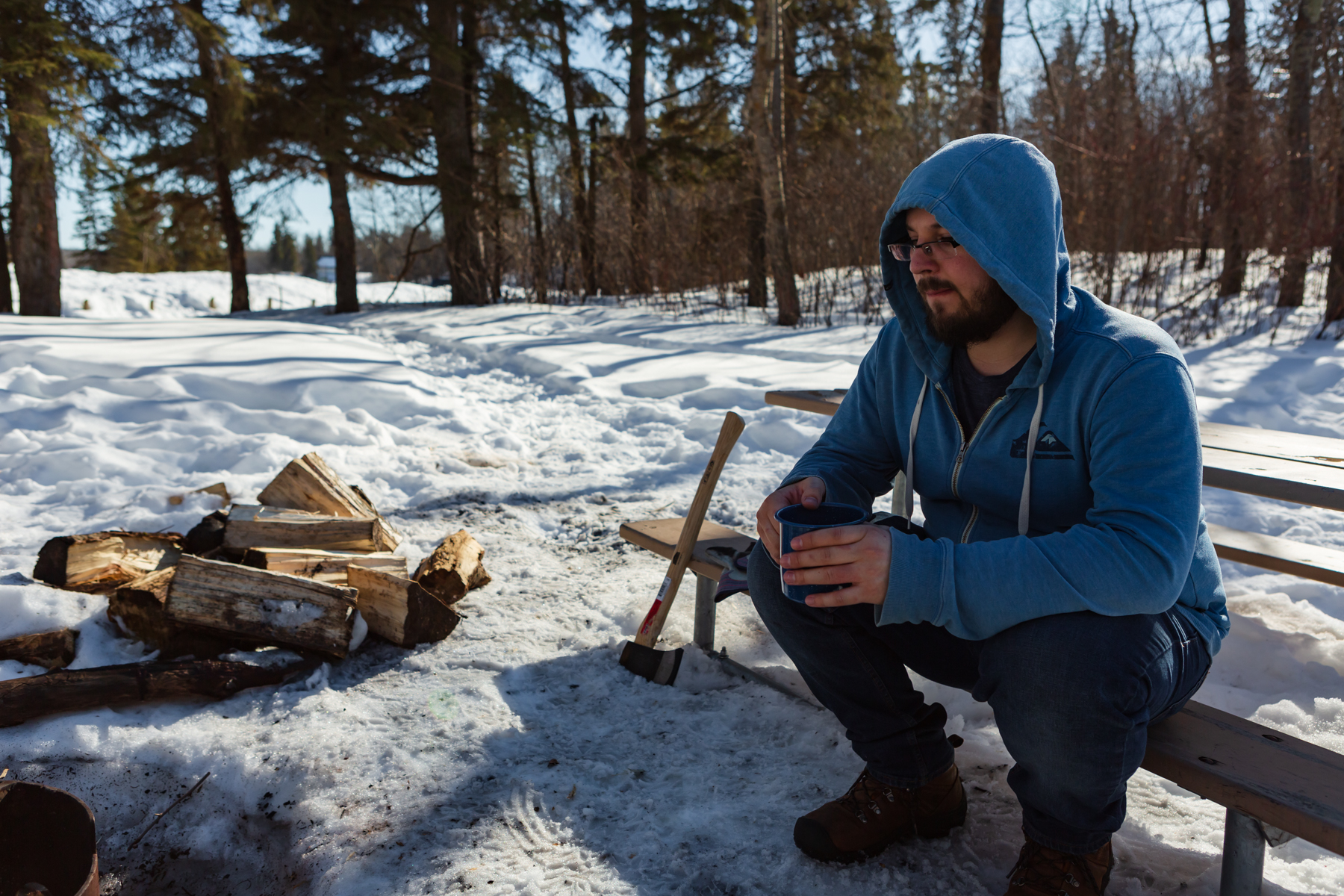 man sitting at picnic table drinking coffee looking at fire