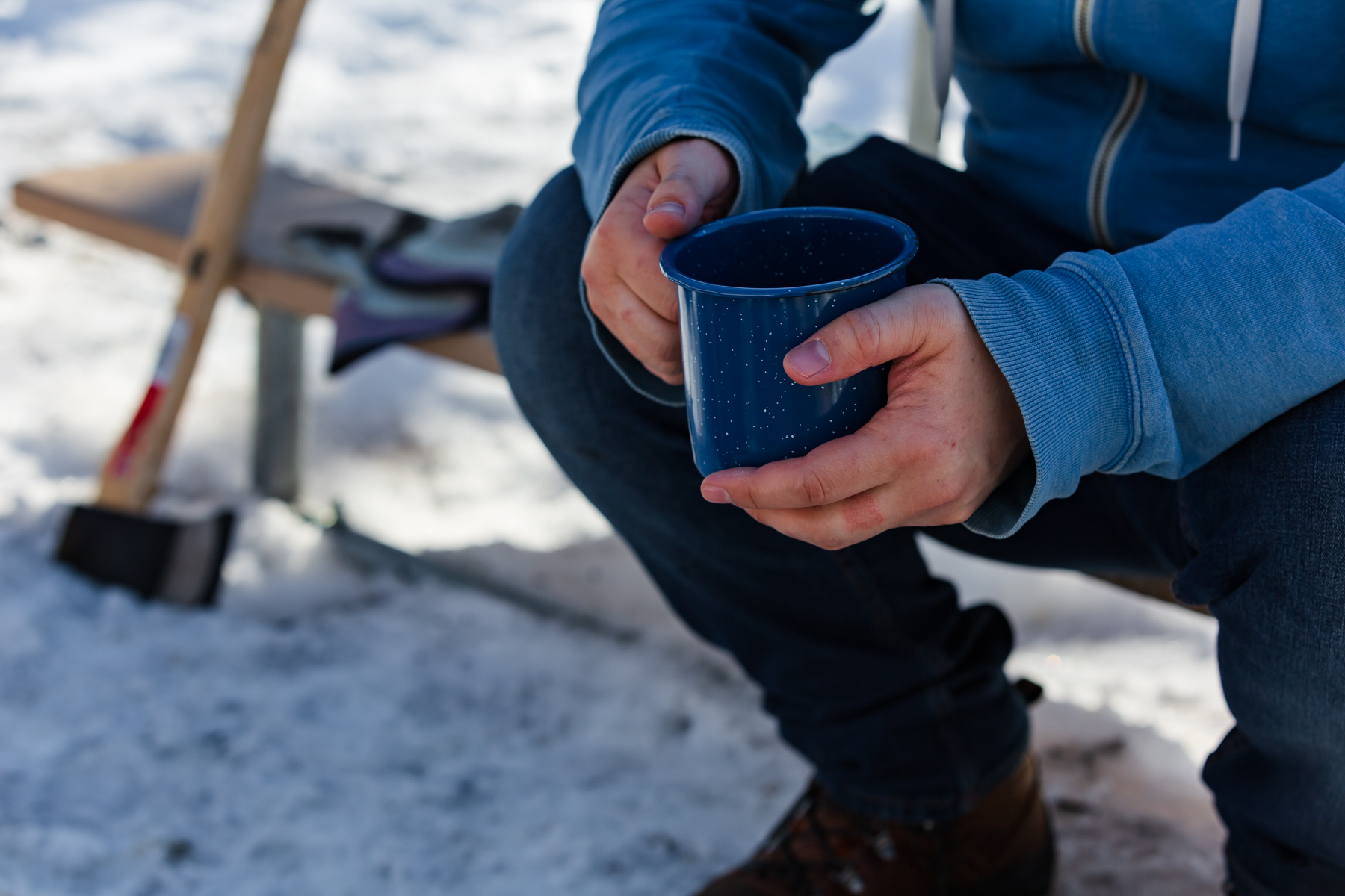 Man sitting on a picnic table drinking coffee from an blue enamel camp mug