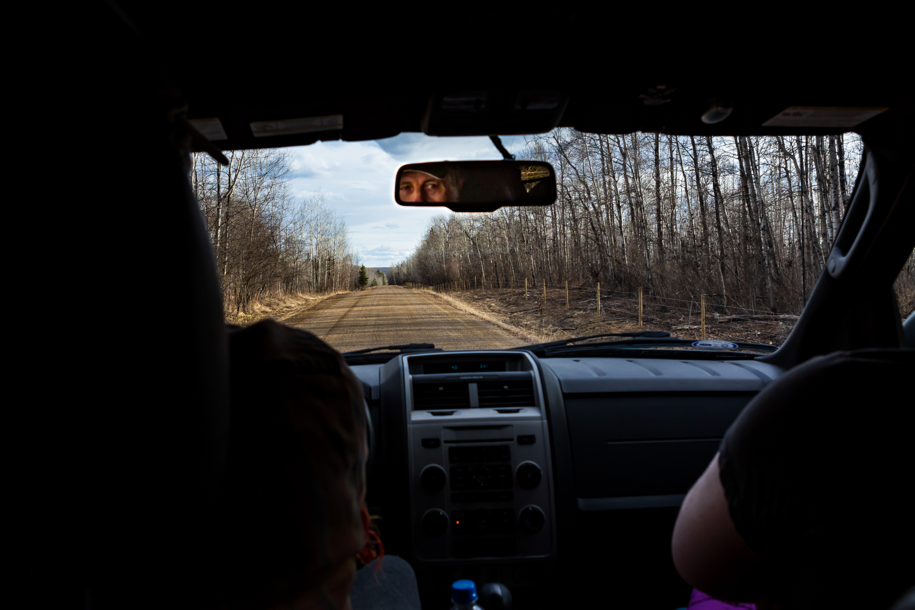 view from the back seat of an suv driving down a gravel road